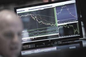 man with computer screen showing stocks in background