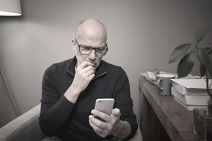 Mature man at home using smartphone for online banking, shopping, social media, e-mail, etc.