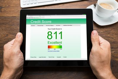 Person Hands With Digital Tablet Showing Credit Score