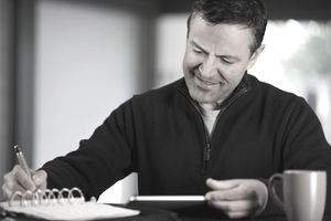 A Man Writes on a Calendar While Looking at His Tablet