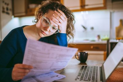 Woman reviewing tax forms and looking distressed