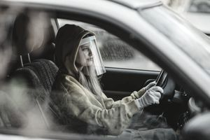 Young Woman Driving a Car with Protective Face Shield and Gloves on.