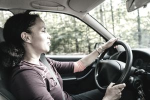 A woman is driving through a wooded area.