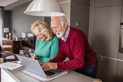 Man and woman using laptop at home to look at their investments