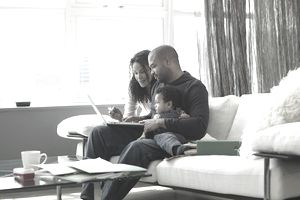 Parents and young child sitting on a sofa with a laptop