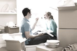Couple eating a takeout meal on a window seat surrounded by packing boxes