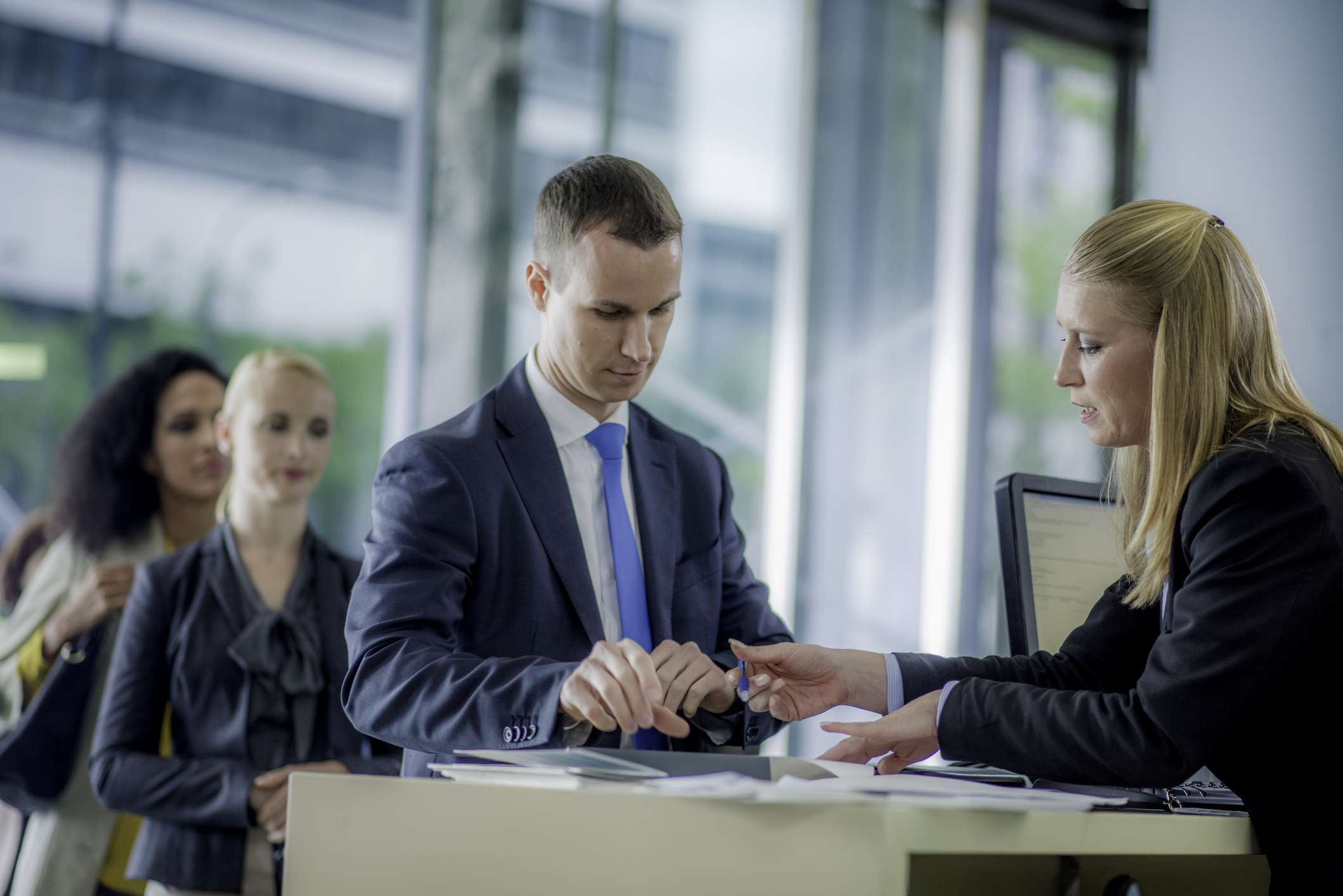 Man working with woman at bank to correct errors in his account