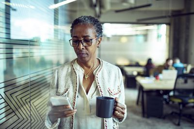 Mature businesswoman consults phone and holds coffee cup in office