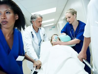 Doctor and nurses pushing a patient through the ER on a stretcher and holding an oxygen mask on their face