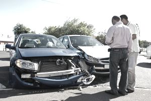 Drivers exchange insurance information following a car crash.