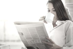A dark-haired woman reads the morning news over the lip of her coffee cup.