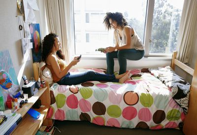 Two female college students talking and relaxing in a dorm room