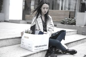 Fired businesswoman sitting on steps with box of belongings