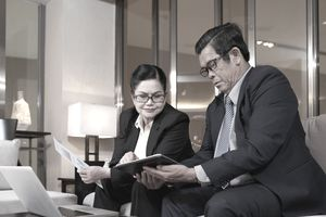 Two businesspeople in bank sit on sofa reviewing documents