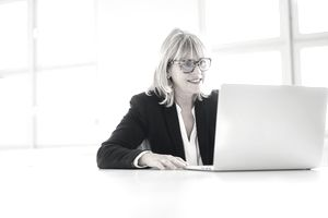 woman wearing spectacles working on a laptop.