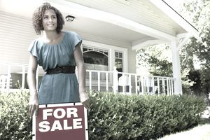 young woman with a for sale sign outside a house