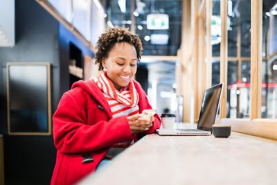 Woman wearing a red coat checking her phone while sitting in front of laptop