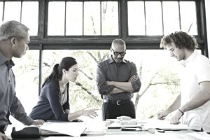 Four architects of varying diversity are examining plans at table in office