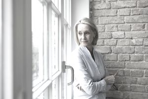 Mature woman looking sadly out a window.
