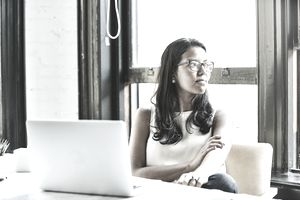 A woman sits in front of her computer and looks out the window as she contemplates her finances