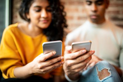 A man and woman use their phones to send money