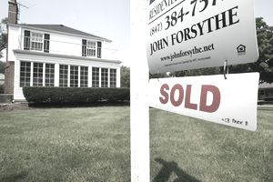 A 'SOLD' sign is visible below a realtor's 'FOR SALE' sign in front of a single-family home