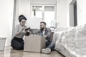 couple sitting in apartment packing up boxes and looking at a lease