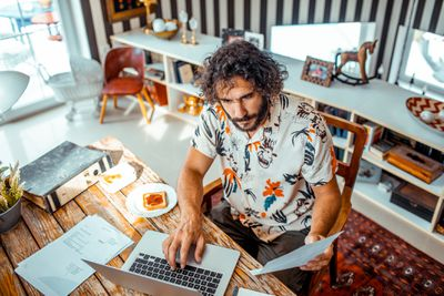Freelancer working on laptop with paperwork
