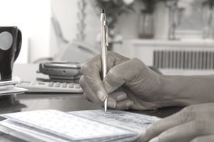 Elderly woman writing in a checkbook