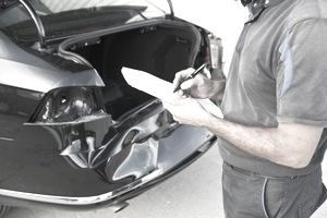 A person writing notes about a rear-ended black car after a crash