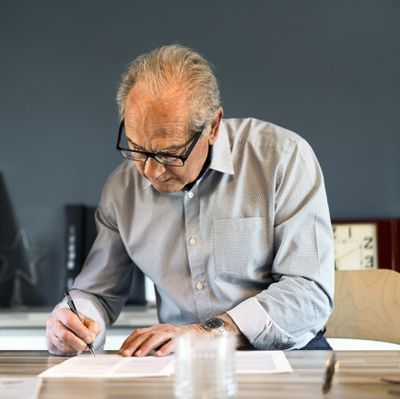 man in blue collared shirt with glasses signing a document