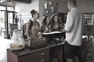 three young women are checking into a hotel for vacation