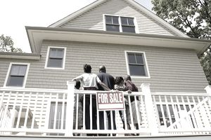 Family on porch looking up at house for sale