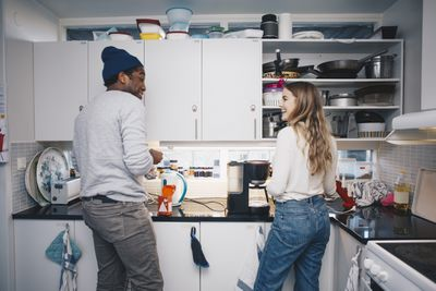 Two roommates stand in their kitchen, chatting over coffee
