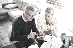 A couple looking at a tablet while investing with robo-advisors