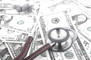 Stethoscope on top of scattered dollar bills representing the costs of healthcare.