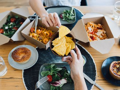 Overhead shot of table with food in takeaway containers. Male hand is offering tortilla chips to a female hand.