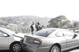 Two men arguing at the scene of a car accident
