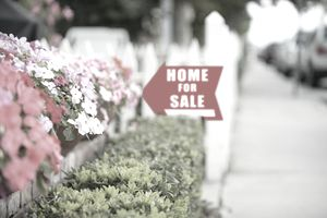 home for sale sign pointing next to flowers and hedges