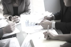 a businessman pointing to a graph while conversing with colleagues