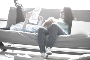 Concentrating young couple examining tax papers while relaxing on sofa at home