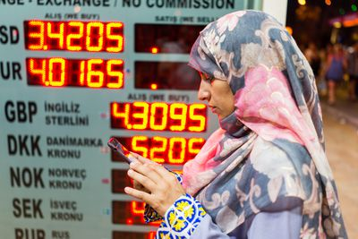 woman standing in front of currency exchange prices on an electronic board
