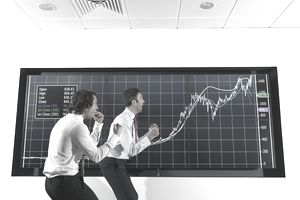 Two successful stock brokers celebrating with upward trending graph
