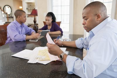 Dad paying bills with teens with digital tablets at the table