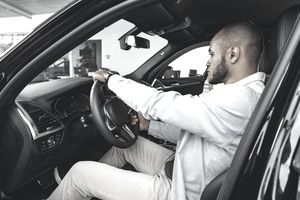 Young African American man sitting in a new car in car showroom and looking around