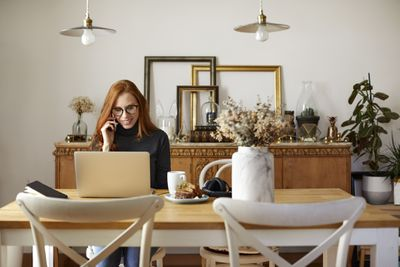 person on phone in front of computer at brown table that has flowers on it in marble vase