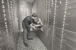 Man looking in safe deposit box in bank vault