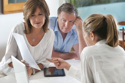 mature couple looking over documents with legal advisor