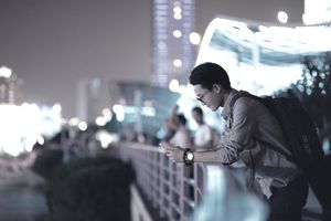 A young businessman checking his phone at a bridge with lights