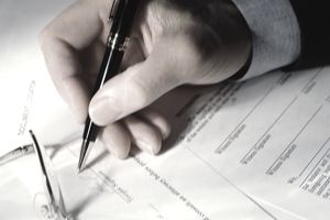 Man signing last will and testament, close-up